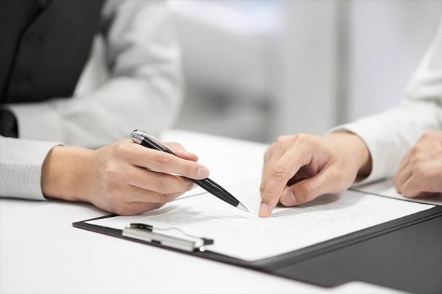 契約書の内容をチェックする日本人男性ビジネスマン