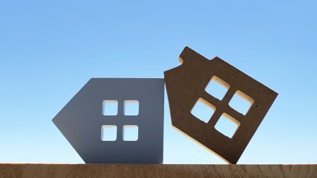 倒れた家2つと青空